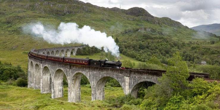 רכבת הקיטור היעקוביטית (The Jacobite) של קו הרמה המערבית (West Highland Line) מעל גשר גְלֶנְפִינַן (Glenfinnan Viaduct).